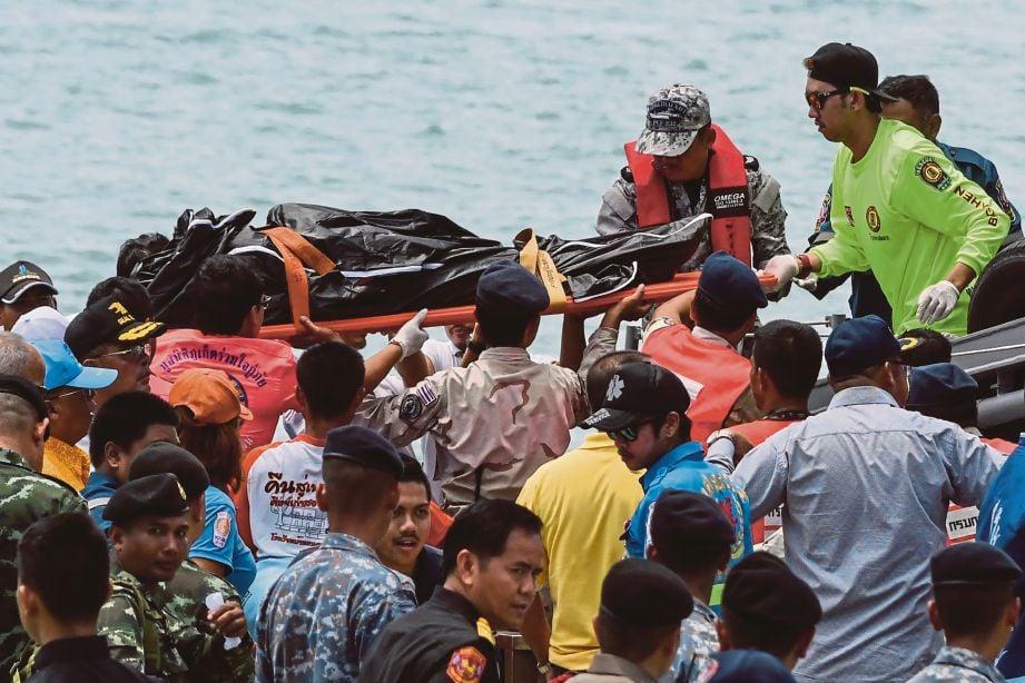 ANGGOTA penyelamat membawa mayat yang ditemui. - AFP