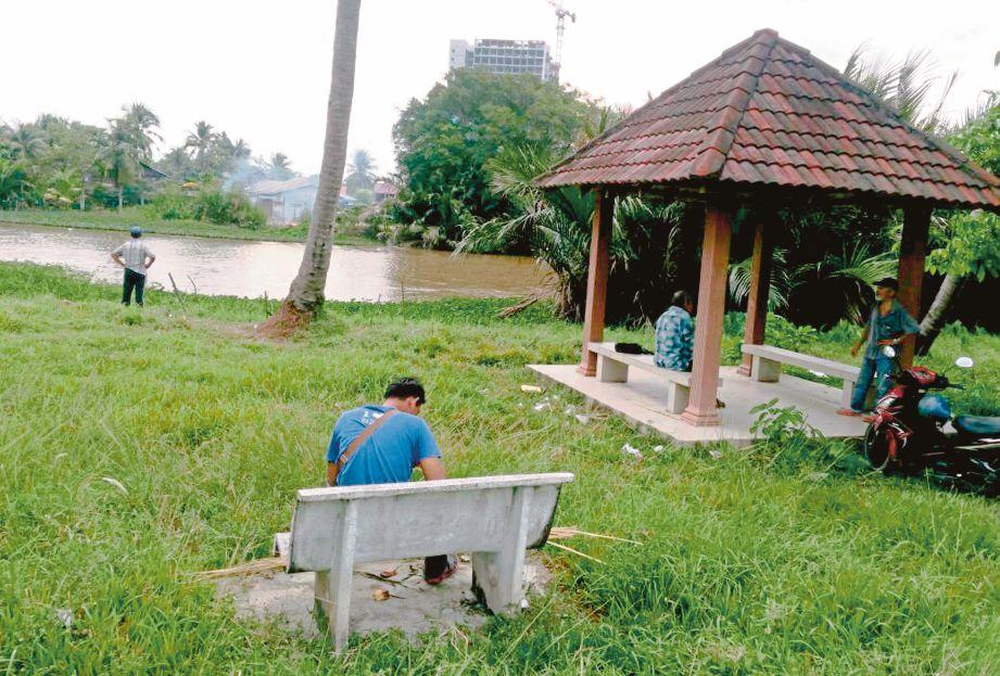 Kawasan rekreasi pesisiran sungai Jalan Kampung Tanjung Bendahara yang tidak terurus ditumbuhi rumput dan lalang.