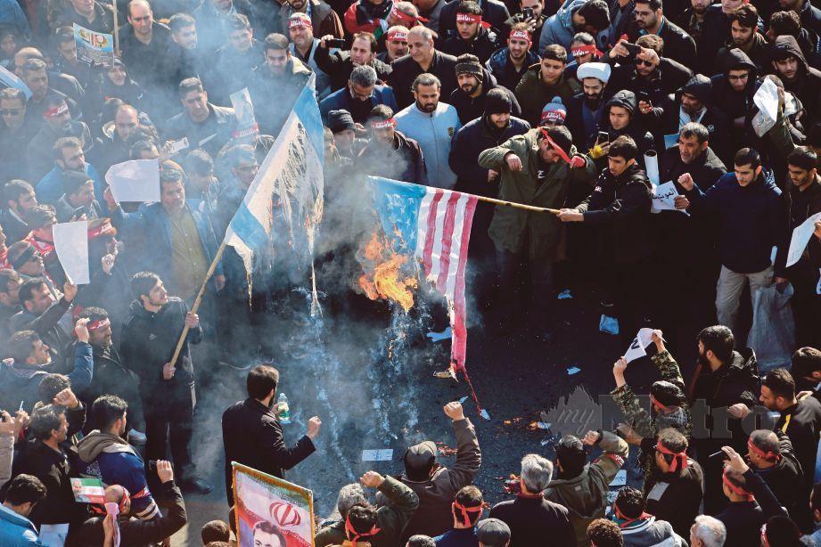 PENDUDUK Iran membakar bendera Israel dan AS ketika perarakan pengebumian Qasem Soleimani. FOTO AFP
