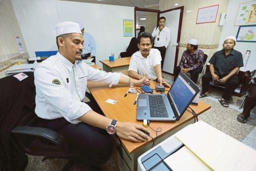 Shahrul Azam memeriksa data individu menerusi sistem biometrik di Makkah.