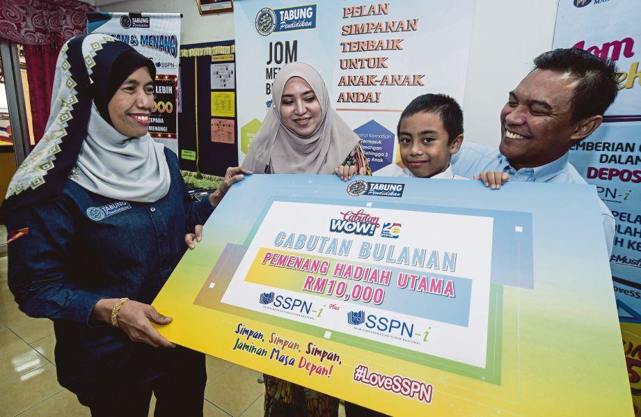 Mastura (kiri) menyampaikan replika cek kepada pemenang hadiah utama, Muhammad Salahuddin (dua dari kanan) sambil diperhatikan bapanya, Mohd Ashik Abdullah (kanan) dan ibu, Nurmahayu Idrus.