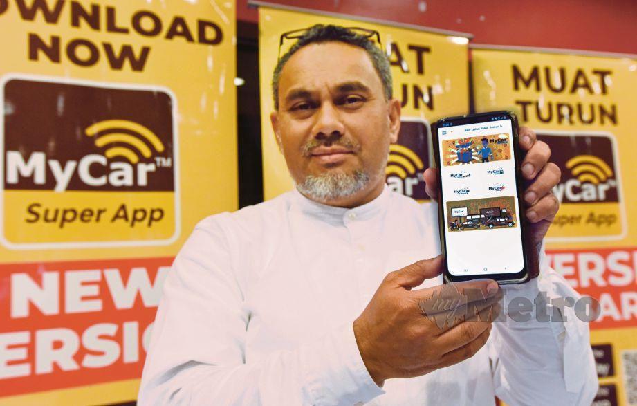 MOHD Noah menunjukan aplikasi Super MyCar   di telefon pintar.