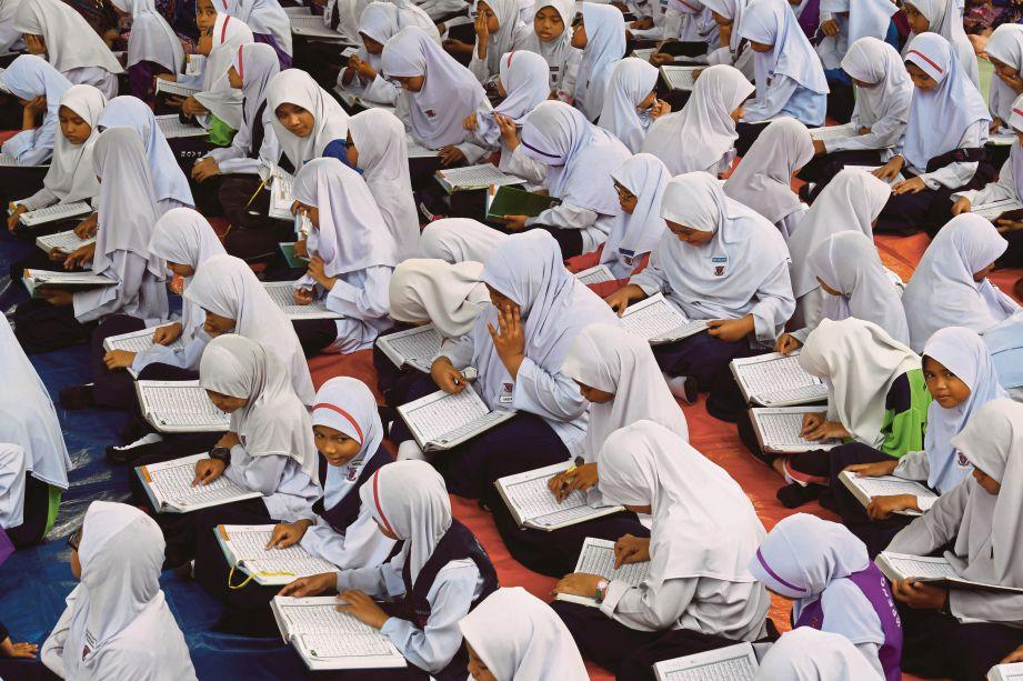 MURID Sekolah Kebangsaan Pauh Jaya tekun membaca al-Quran.