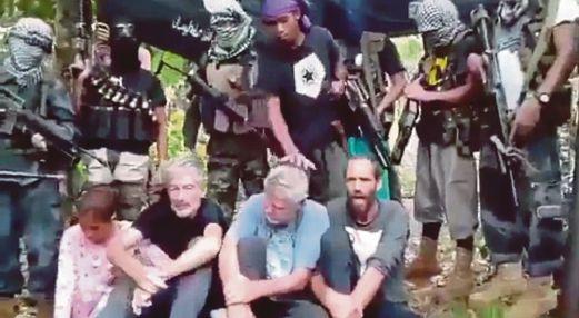 GAMBAR fail menunjukkan anggota Abu Sayyaf bersama empat tebusan termasuk tiga lelaki warga Barat yang diculik mereka tahun lalu.