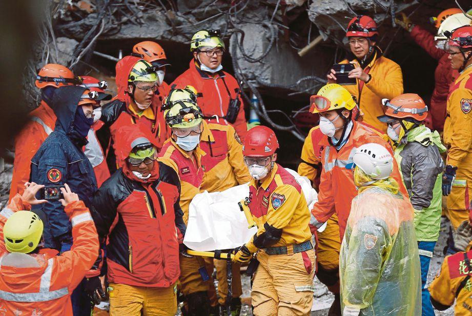ANGGOTA penyelamat mengeluarkan mayat dari bangunan yang runtuh. - EPA