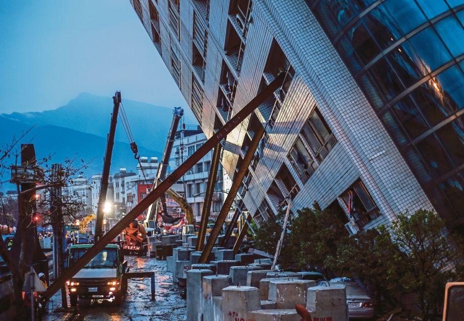 ANGGOTA penyelamat menggunakan rasuk logam untuk menyokong bangunan yang condong akibat gempa ketika operasi mencari mangsa di dalam runtuhan. - EPA