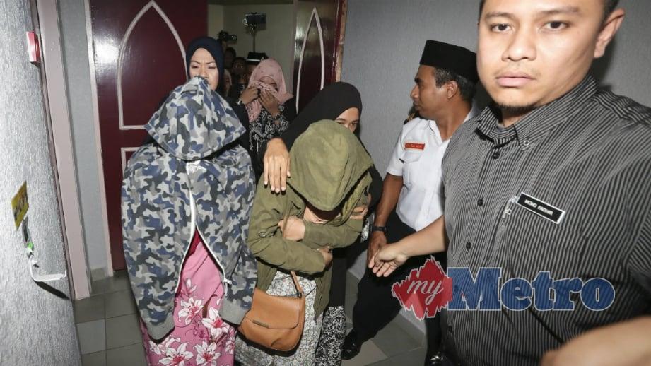 PASANGAN lesbian berusia 22 dan 32 tahun berjalan keluar meninggalkan dewan bicara selepas menjalani hukuman sebat di khalayak umum atas pertuduhan melakukan hubungan sejenis di Mahkamah Tinggi Syariah Kuala Terengganu berjalan lancar dengan disaksikan kira-kira 100 orang, hari ini. FOTO Ghazali Kori