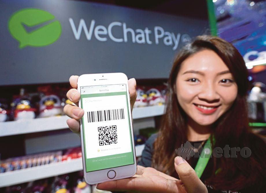 GAN Jay Syuen mengimbas kod QR pada telefon bimbit untuk membeli barang pada majlis pelancaran WeChat Pay.