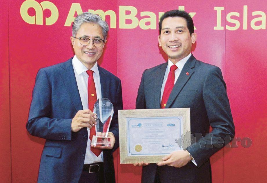 KETUA Pegawai Eksekutif Kumpulan AmBank Group, Datuk Sulaiman Mohd Tahir (kiri) dan Eqhwan menunjukkan anugerah yang diterima.