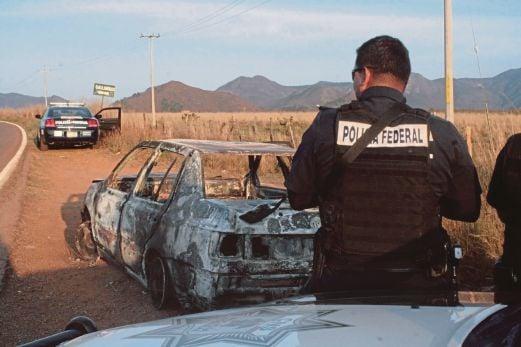 POLIS memeriksa kereta yang hangus dibakar selepas ditembak dalam kejadian serang hendap terhadap konvoi polis.