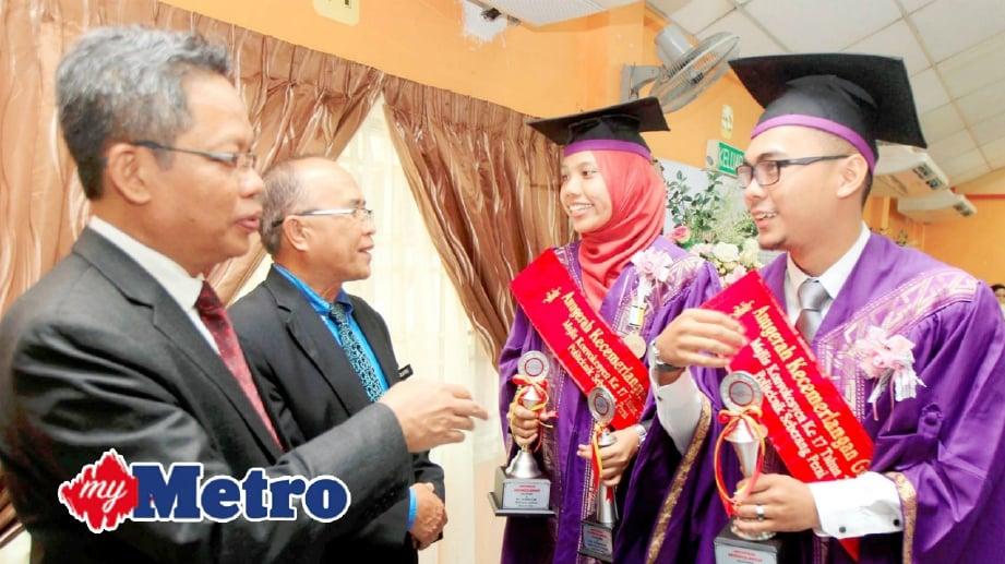 DATUK Mohd Razali Hussain (kiri) bersama Pengarah Politeknik Seberang Perai, Zulkifli Ariffin (dua dari kiri) mengucapkan tahniah kepada graduan terbaik, Muhammad Hazwan Mohd Ariff (kanan) dan Siti Adayu Nasharidan. FOTO Ramdzan Masiam