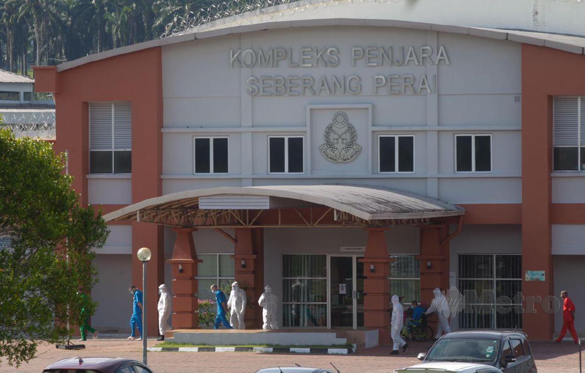 Kakitangan penjara memakai sut peralatan perlindungan diri (PPE) mengiringi banduan untuk melakukan ujian saringan COVID-19 di Kompleks Penjara Seberang Perai, Jawi di sini. Setakat 13 Oktober, penjara terbabit merekodkan tiga kes positif COVID-19  kluster baharu iaitu Kluster Penjara Jawi. FOTO DANIAL SAAD