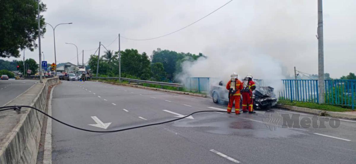 Anggota Balai Bomba dan Penyelamat Tun Hussein Onn memadamkan kebakaran sebuah kereta Proton Persona yang terbabit kemalangan di Balakong di sini, pagi tadi. FOTO IHSAN BOMBA