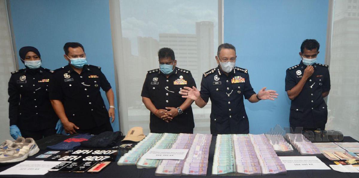Ketua Polis Kuala Lumpur, Datuk Saiful Azly Kamaruddin (dua dari kanan) bersama wang dan barang kes samun dan bunuh pada sidang media di IPD Sentul, Turut hadir, Ketua Polis Daerah Sentul, ACP S. Shanmugamoorthy Chinniah (tengah). FOTO KHAIRUL AZHAR AHMAD