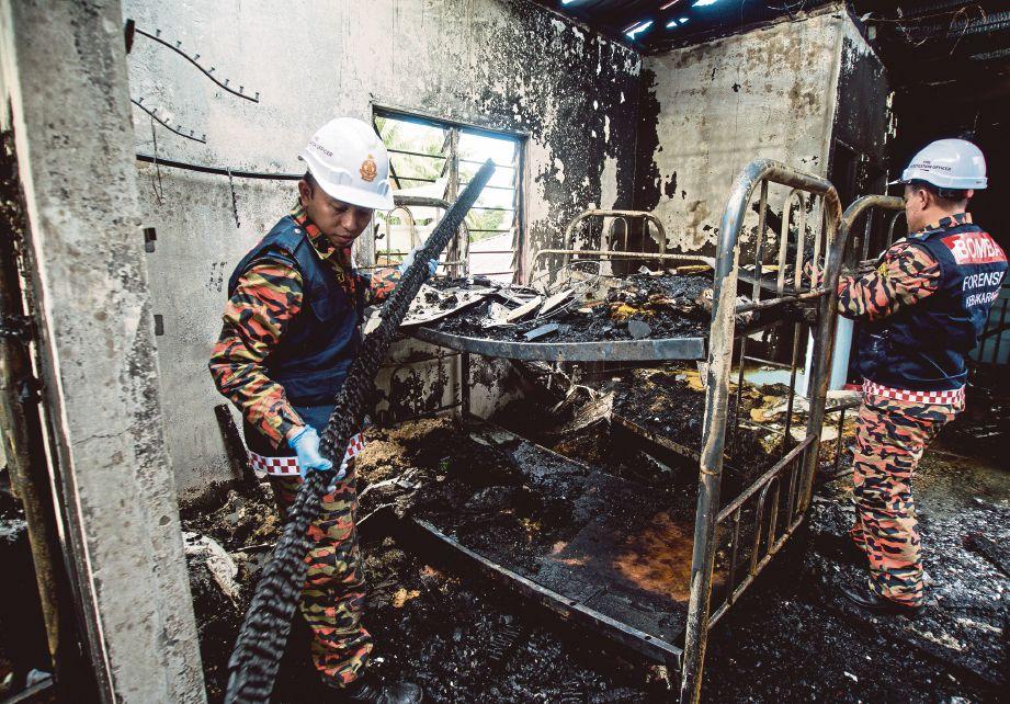 Anggota bomba memeriksa asrama pelajar tahfiz yang terbakar.