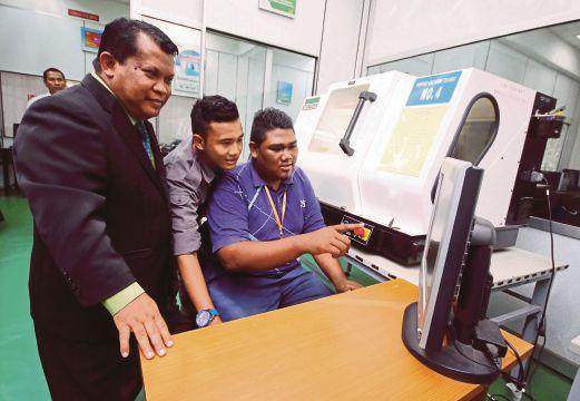 ABD Latif  (kiri) melihat anak didiknya menunjukkan fungsi sebuah mesin yang digunakan dalam proses pembelajaran dalam bidang mekanikal pembuatan di Kolej Komuniti Kepala Batas, Bertam.