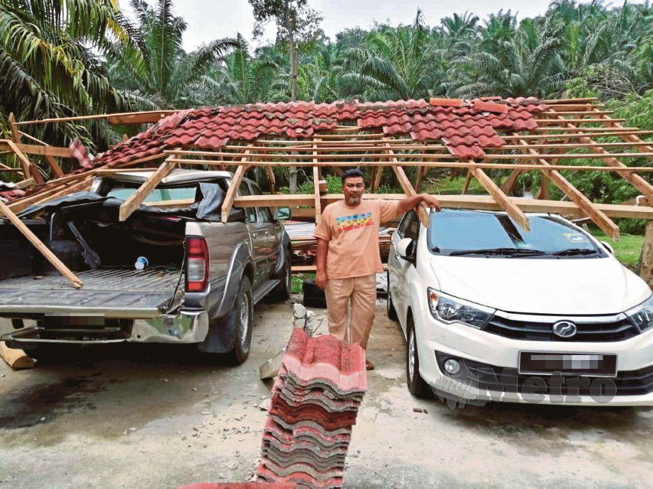 NAZAMUDDIN  menunjukkan atap garaj kereta rumahnya yang  diterbangkan ribut di Kampung Kuala Atok.