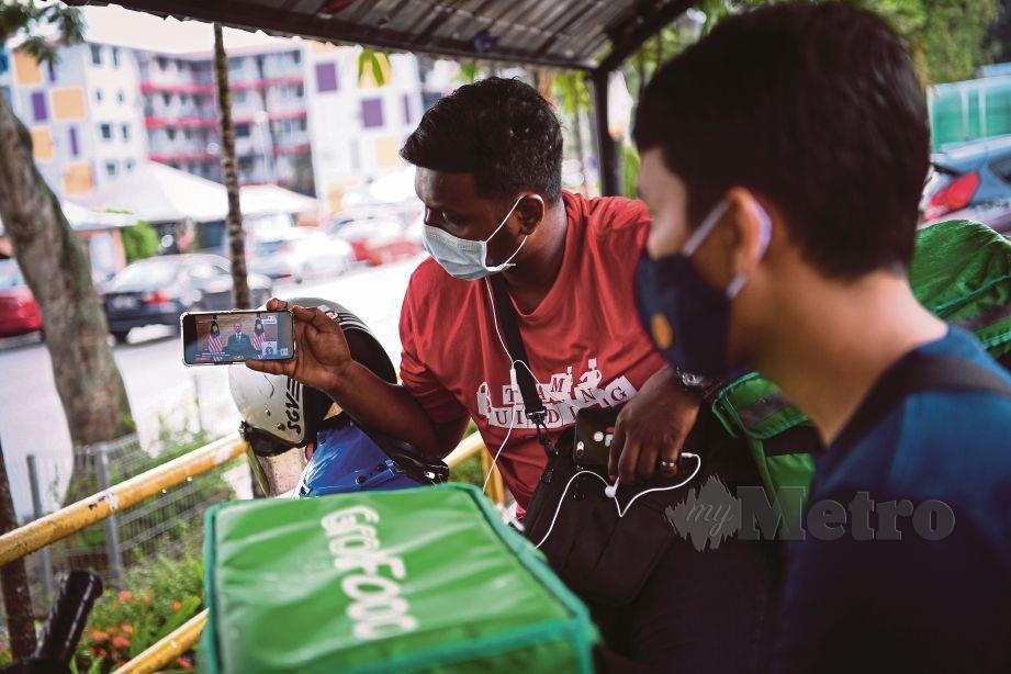 PENUNGGANG perkhidmatan penghantaran makanan menonton siaran langsung pengumuman Pakej Rangsangan Ekonomi Prihatin Rakyat, semalam.