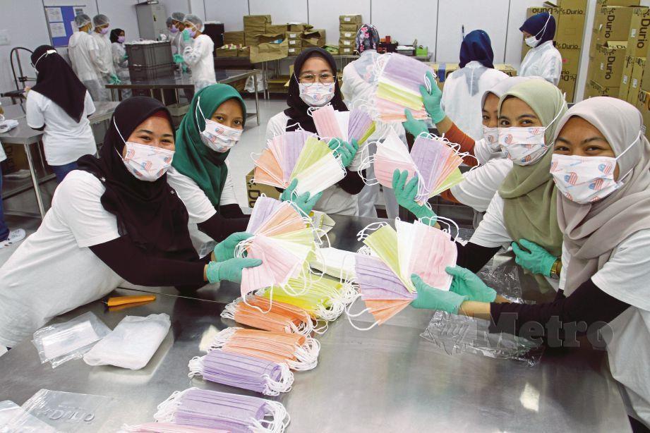 KAKITANGAN Durio PPE Sdn Bhd menunjukkan pelitup muka pelbagai warna yang dihasilkan.
