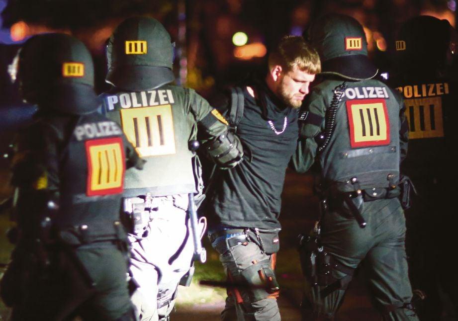 POLIS menahan seorang penunjuk perasaan, semalam. - Reuters