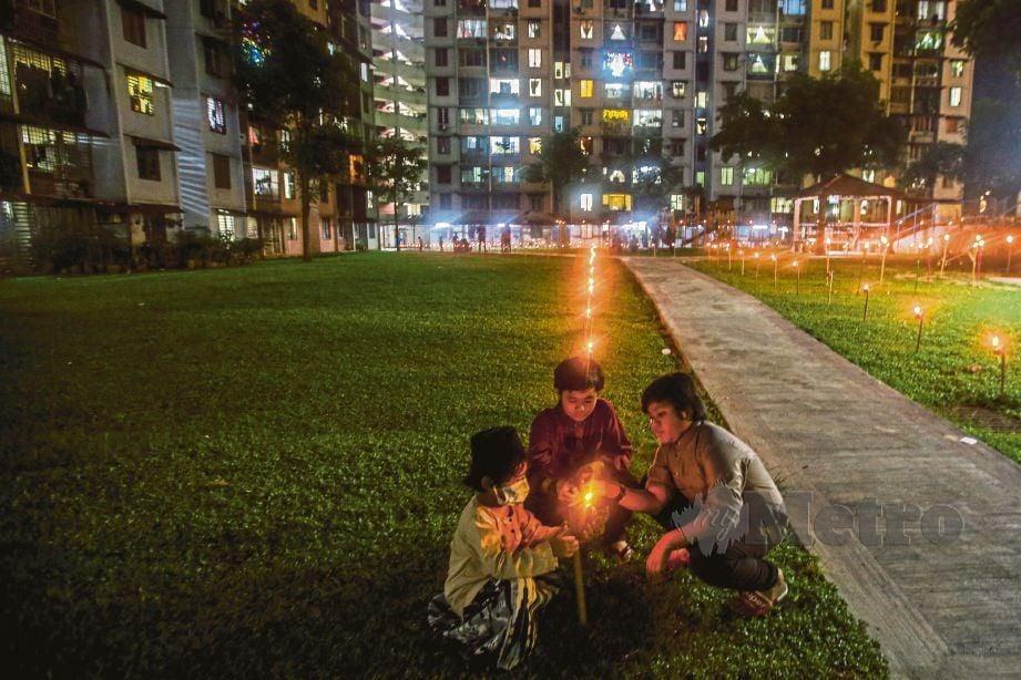 DARI kiri, Mikhael Zidane, Darwisy, dan Danial Ezwan menyalakan api pada pelita yang dipasang di Apartment Abdullah Hukum, Kuala Lumpur. FOTO Osman Adnan