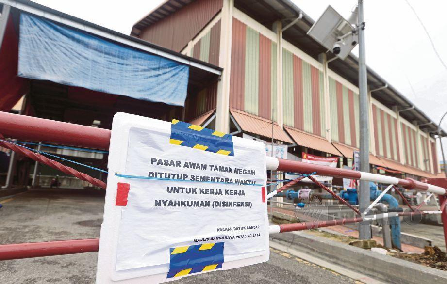 NOTIS pemberitahuan ditampal di pagar Pasar Awam Taman Megah Seksyen SS24 yang ditutup sementara waktu susulan seorang peniaga positif Covid-19. FOTO Hairul Anuar Rahim
