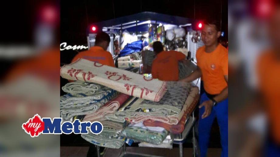 ANGGOTA APM menyediakan keperluan mangsa banjir di pussa pemindahan sementara. FOTO Ihsan APM
