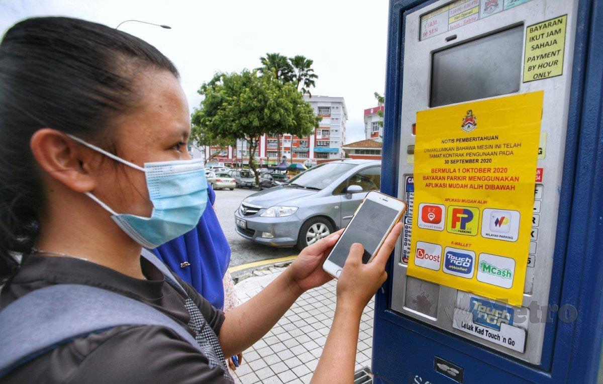 PENGGUNA memuat turun aplikasi mudah alih untuk membayar tempat letak kereta bahu jalan DBKL di Setiawangsa. FOTO MOHD YUSNI ARIFFIN