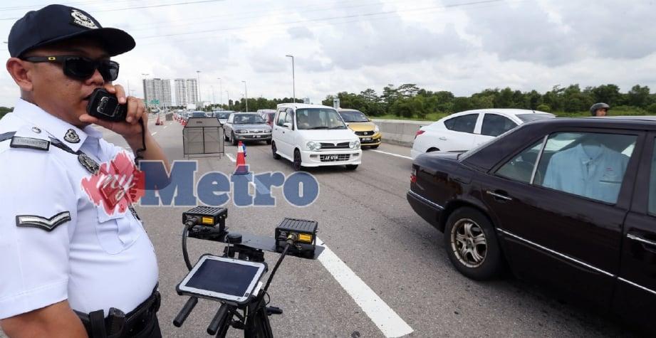 ANGGOTA Polis Trafik menggunakan peranti khas iaitu MCOPS yang dapat menyemak saman tertunggak warga negara asing dengan pantas selain alat iCOPS yang turut digunakan mengimbas nombor pendaftaran kenderaan secara automatik, di Kawasan Rehat dan Rekreasi (R&R) EDL Pandan. FOTO Mohd Azren Jamaludin