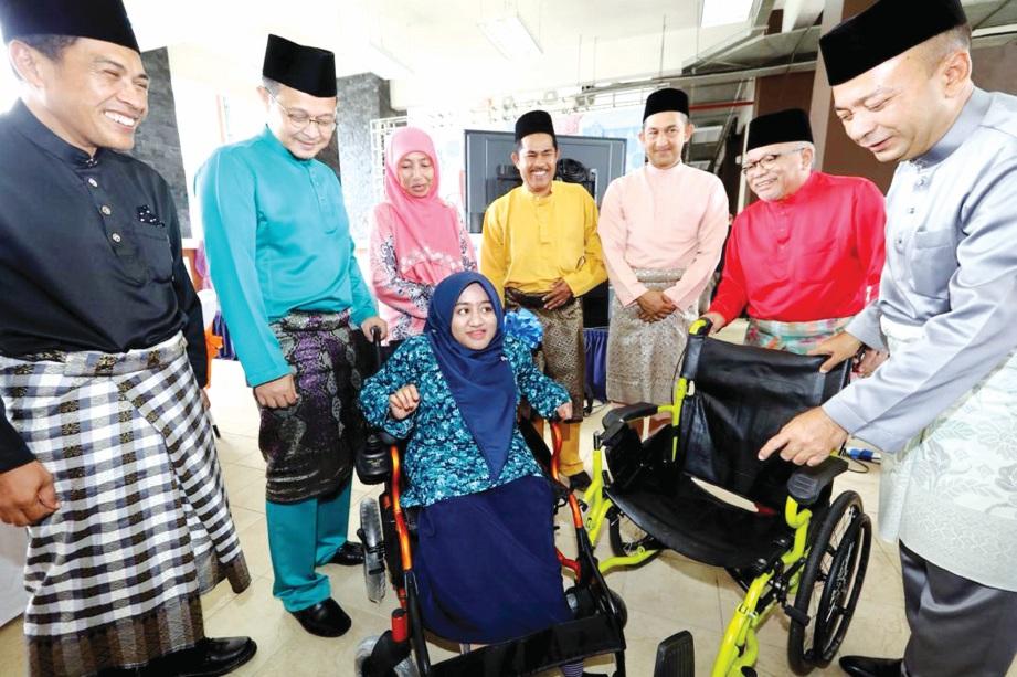 PENUNTUT OKU, Siti Nurfarah Hanim menerima sumbangan kerusi roda elektrik daripada Syarikat Muda Osman.
