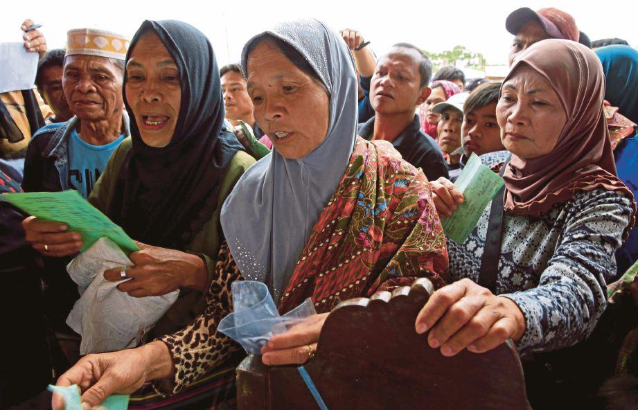 ORANG ramai menunggu didaftarkan untuk mendapat bantuan makanan selepas melarikan diri dari Marawi. - Reuters