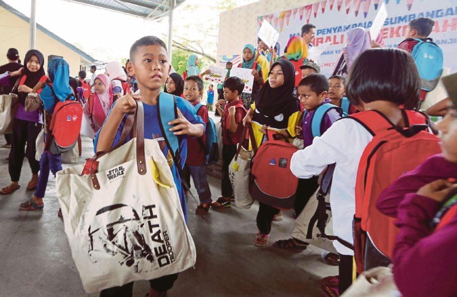 PELAJAR menerima bantuan beg sekolah di Dewan PPD Seberang Perai Tengah, Bukit Mertajam.