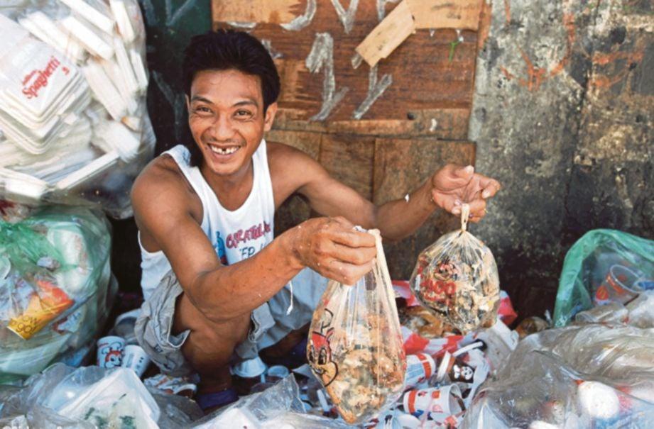 SEORANG lelaki menunjukkan daging yang dikutip dari tempat pembuangan sampah dan dibungkus untuk dijual semula sebagai makanan. - Agensi