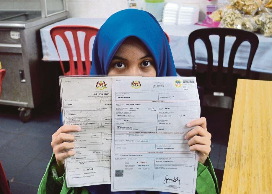 Merhana  memegang dokumen kelahirannya dan sijil mati arwah ayahnya.
