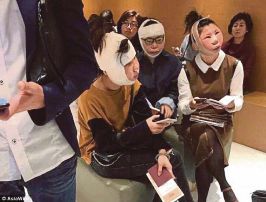 GAMBAR menunjukkan tiga wanita dengan muka bengkak dan berbalut duduk di sebuah lapangan terbang di Korea Selatan. - Agensi