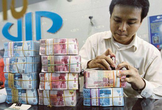 SEORANG pekerja  menyusun wang untuk seorang pelanggan di sebuah pusat tukaran wang di Jakarta, Indonesia, semalam.