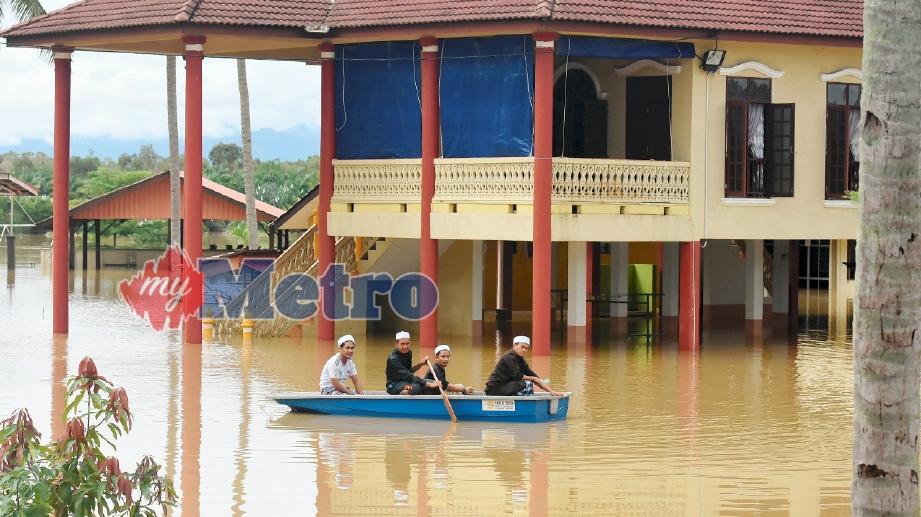 PELAJAR Pusat Tahfiz Al-Quran Baitul Rahman menggunakan sebuah bot untuk bergerak selepas separuh daripada asrama mereka ditenggelami air sejak tiga hari lalu di Kampung Nyatuh, Setiu. FOTO Mohd Syafiq Ridzuan Ambak