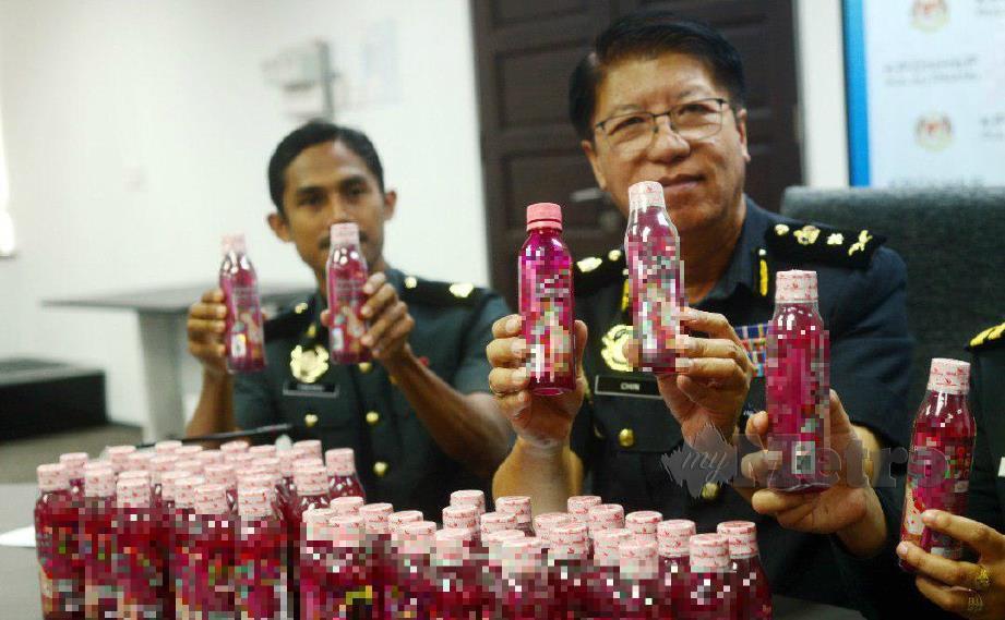 Ketua Penguat Kuasa KPDNHEP Pulau Pinang, Chin Ching Chung menunjukkan produk minuman kesihatan tiruan yang dirampas KPDNHEP. FOTO Shahnaz Fazlie Shahrizal