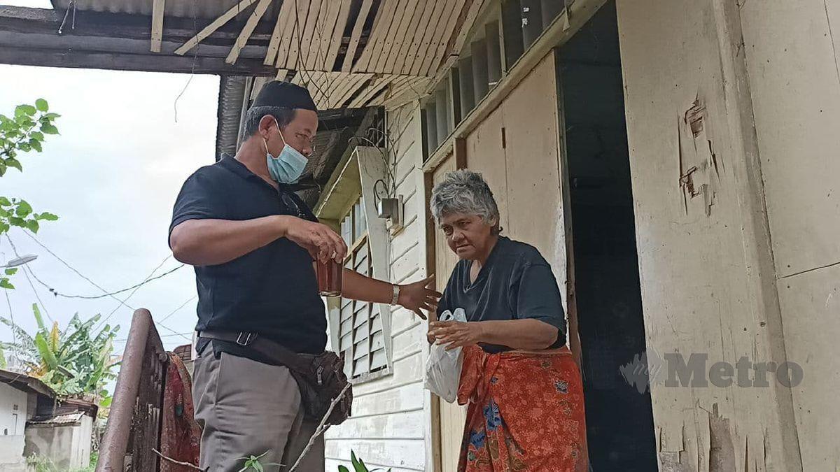 Zainal Azlan Yahya, 54, menyerahkan bungkusan nasi bersama minuman kepada kakaknya, Rohani, 66, yang mempunyai masalah mental ketika ditemui di rumah warga emas itu di Jalan Bayam di sini. FOTO SITI ROHANA IDRIS