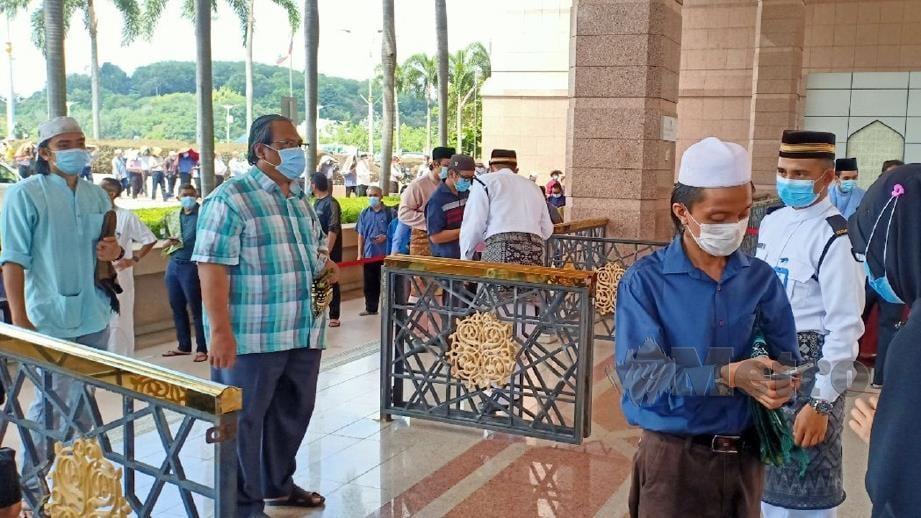ORANG ramai mula beratur pada 11.30 pagi bagi mendapatkan giliran menunaikan solat Jumaat di Masjid Putra. FOTO Samadi Ahmad