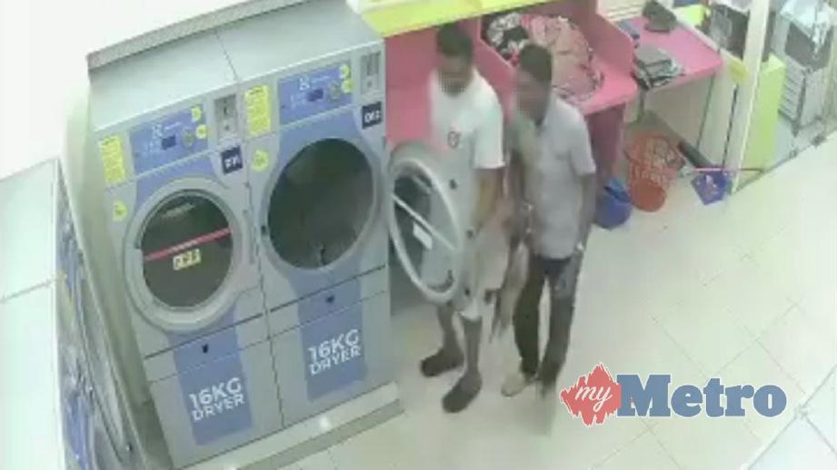 PETIKAN rakaman CCTV menunjukkan dua lelaki memasukkan kucing betina terbiar yang sedang bunting ke dalam mesin pengering di kedai dobi. FOTO Persatuan Haiwan Malaysia