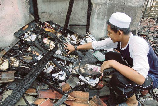 PELAJAR tahfiz mencari al-Quran yang masih elok selepas asrama musnah dijilat api.