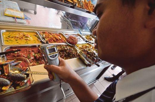 PEGAWAI penguat kuasa memeriksa suhu makanan yang dijual
