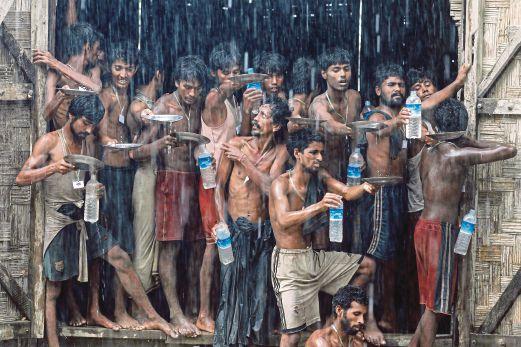 PELARIAN Rohingya dan Bangladesh menakung air hujan ketika hujan lebat di kem pelarian di Thailand.