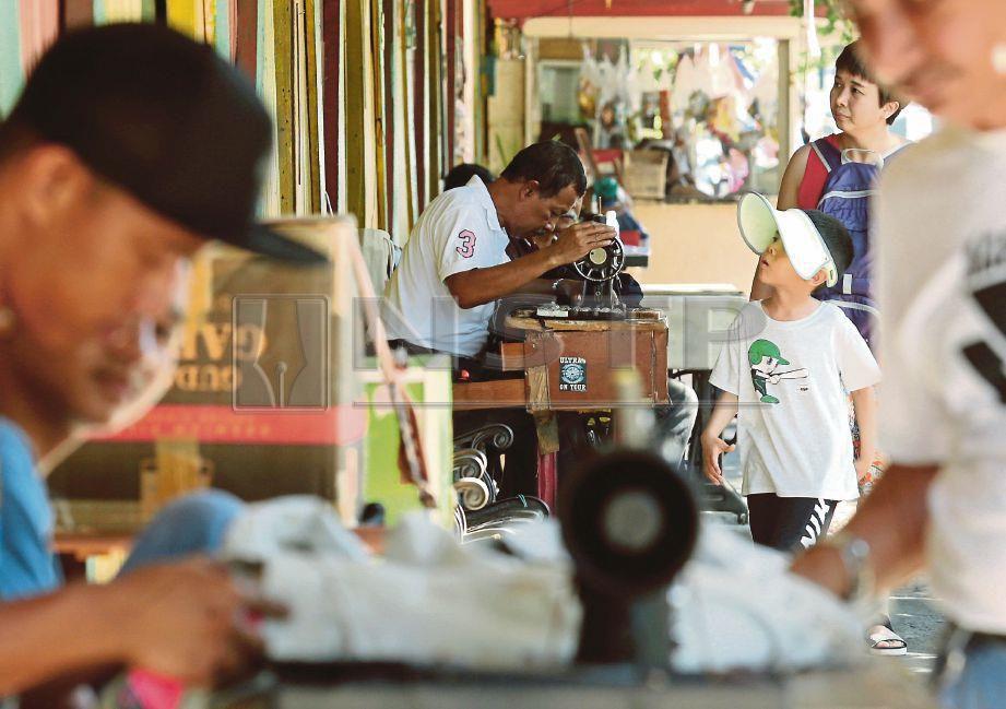 DERETAN penjahit lelaki melayani pelanggan di Pasar Kraftangan Kota Kinabalu.