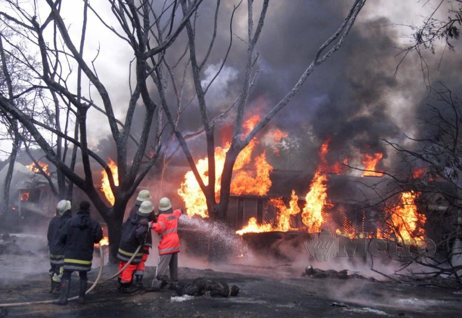 BOMBA memadam kebakaran lori tangki yang meletup selepas terbabas yang turut membunuh puluhan orang di Morogoro. - Reuters