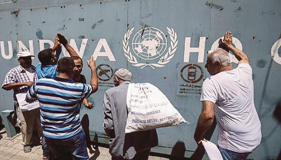 SEKUMPULAN penduduk Palestin berkumpul dekat logo Agensi Bantuan Pelarian Palestin (UNRWA) di Gaza. - Fail (AFP)