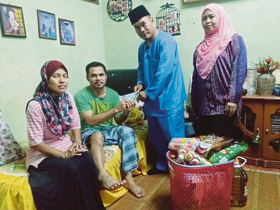 Mohd Nor (dua dari kanan) menyampaikan sumbangan kepada Zulfadly ketika lawatan di rumahnya, semalam.