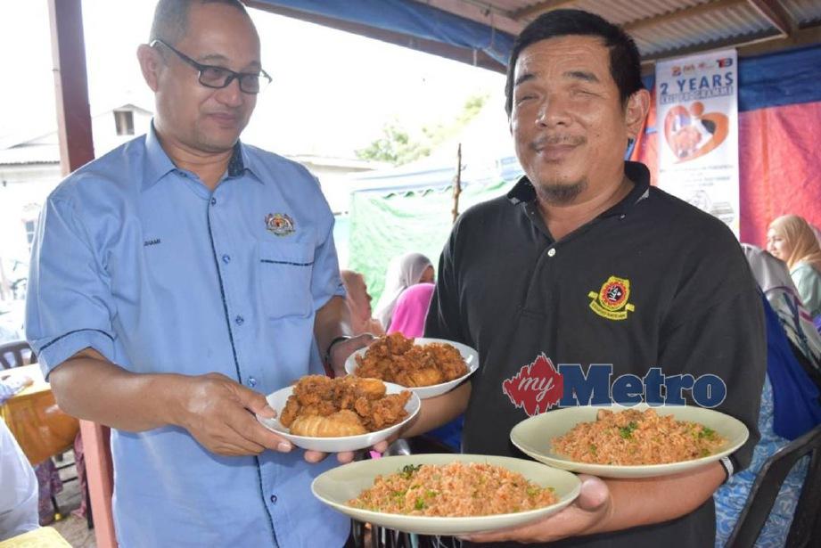 MOHD Arif (kanan) menunjukkan nasi goreng sotong yang dijual di gerainya kepada Pengarah Jabatan Kebajikan Masyarakat JKM Terengganu, Zuhami Omar. FOTO Rosli Ilham