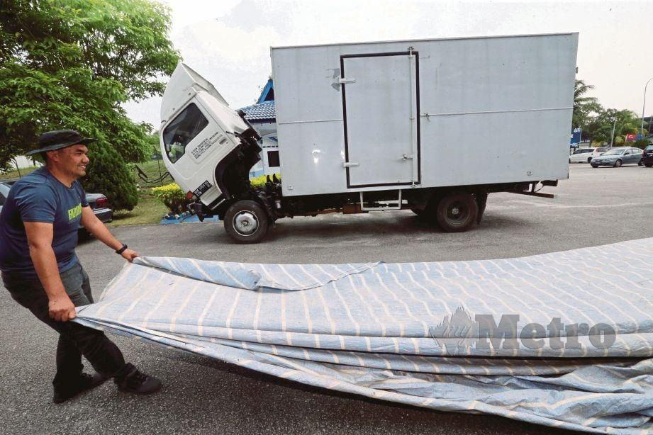 ANGGOTA polis marin menunjukkan kanvas yang digunakan untuk menutup kesan tayar lori.